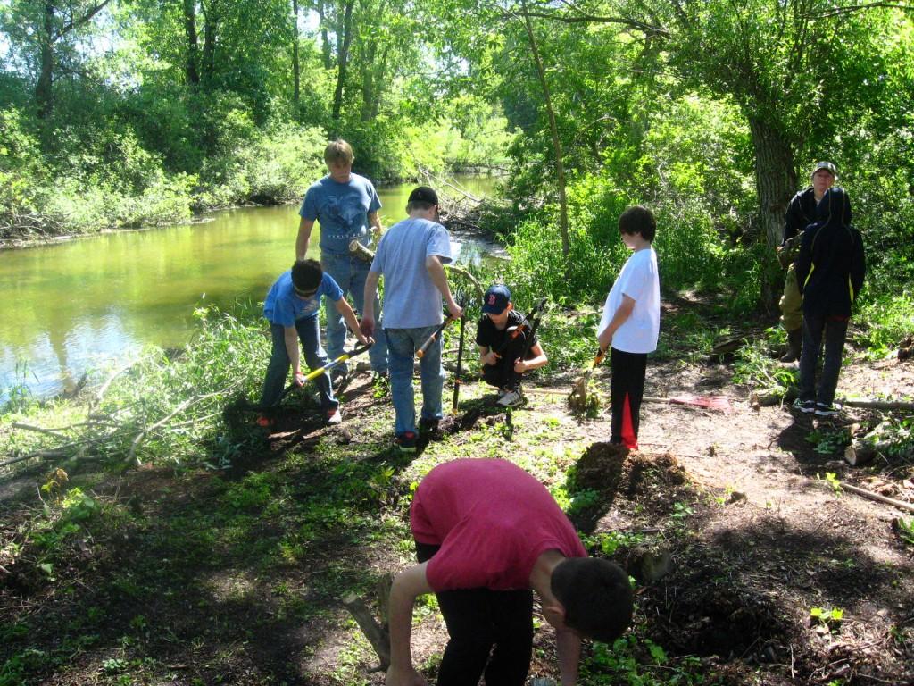Kids removing invasive species and restoring river banks